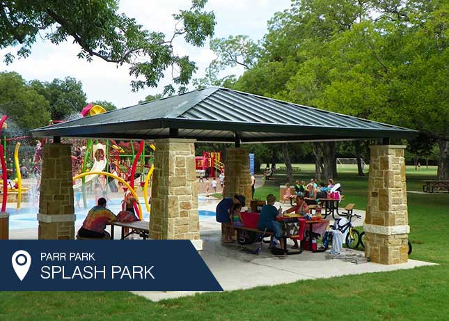 People eating under the Parr Park Shade Structure designed and installed by Kraftsman