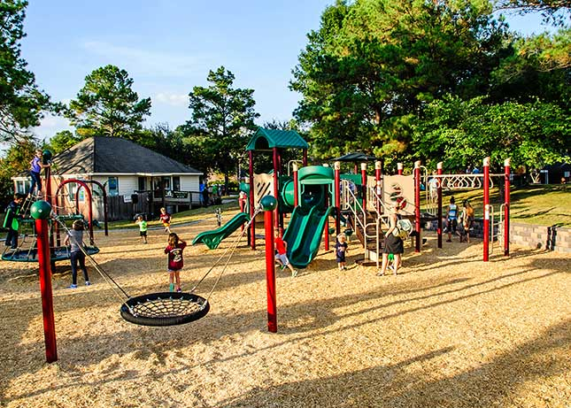 Kids playing at Cypress, TX Green Trails Playground Park Design by Kraftsman